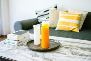 Modern interior design with wooden coffee table, brightly colored candles and a sofa