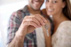 Close up of young couple with keys to their first house